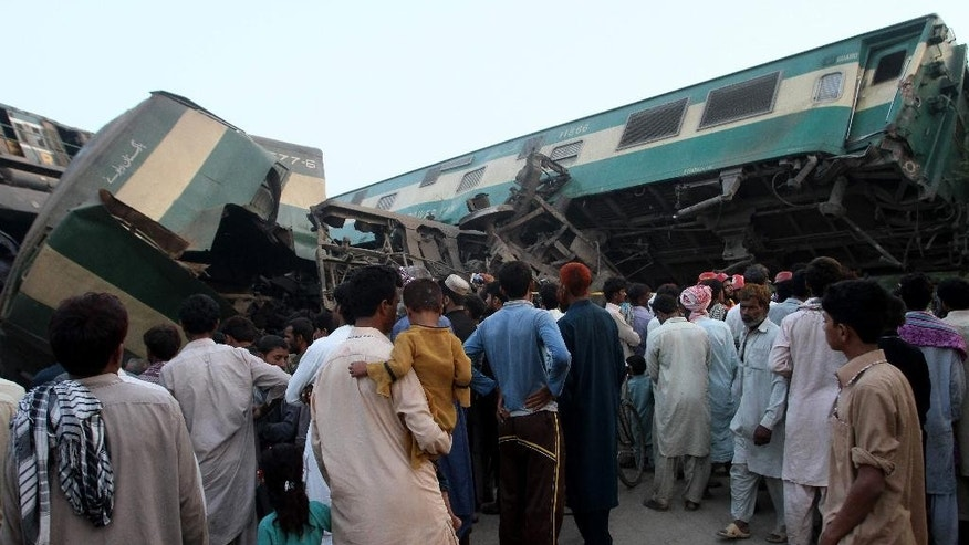 People look at a mangled passenger train that had collided with freight train near Multan, Pakistan, Thursday, Sept. 15, 2016. Scores of passengers were killed and many others were hurt Thursday when a passenger train collided with a freight train near the central Pakistan city of Multan, rescuers and a railway officials said. (AP Photo/Asim Tanveer)