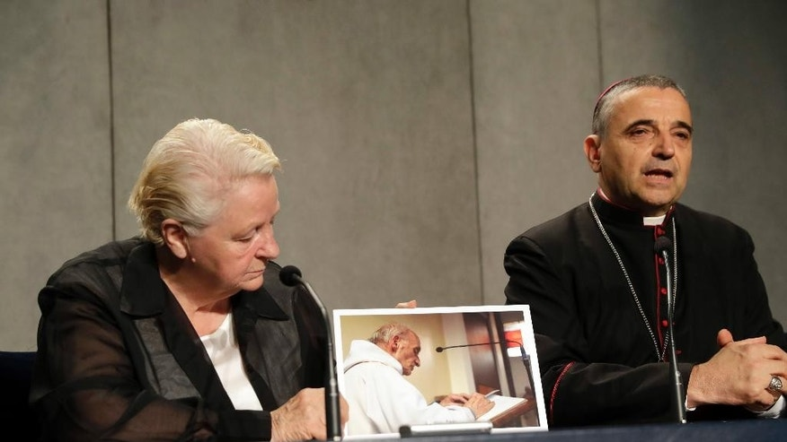 "Roselyne Hamel, of France, holds a picture of her brother, Rev. Jacques Hamel, as she attends a press conference with Rouen Bishop Dominique Lebrun at the Vatican, Wednesday, Sept. 14, 2016. Pope Francis honored the French priest who was killed by Islamic extremists while celebrating Mass as a martyr on Wednesday and urged all people of faith to have the courage to denounce such killings as ""satanic."" (AP Photo/Alessandra Tarantino)"