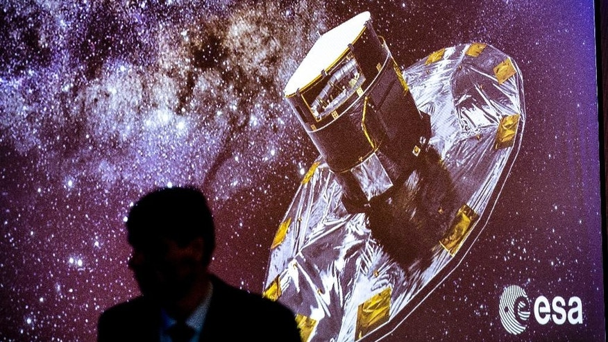 A man walks in front of a slide show depicting a representation of the ESA Gaia Project, at the ESA center in Villanueva de la Canada, near Madrid, Spain, Wednesday, Sept. 14, 2016. the European Space Agency said Wednesday its mission to chart more than 1 billion stars in the Milky Way is on track for completion in a year's time. The agency released the first data from its ongoing effort, called the Gaia Mission, to draw the biggest and most precise three-dimensional map of our galaxy. (AP Photo/Daniel Ochoa de Olza)