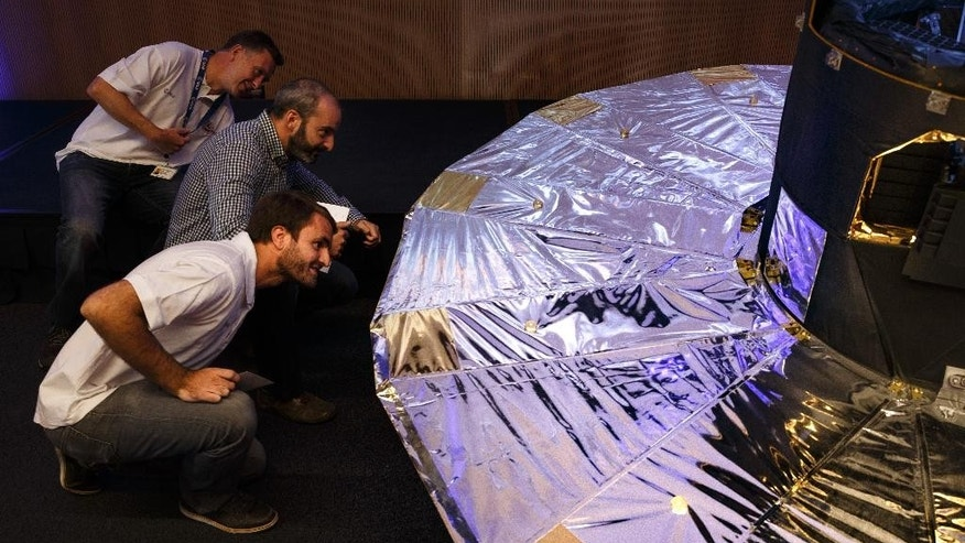 Scientists look under a scaled reproduction of the GAIA surveyor after an event of the European Space Agency, or ESA, to release the first data on its GAIA mission to make a space map, at the ESA center in Villanueva de la Canada, near Madrid, Spain, Wednesday, Sept. 14, 2016. The European Space Agency said Wednesday its mission to chart more than 1 billion stars in the Milky Way is on track for completion in a year's time. The agency released the first data from its ongoing effort, called the Gaia Mission, to draw the biggest and most precise three-dimensional map of our galaxy. (AP Photo/Daniel Ochoa de Olza)