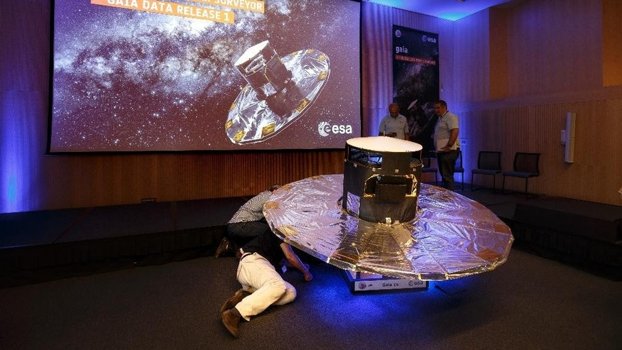 Scientists look under a scaled reproduction of the GAIA surveyor at an event of the European Space Agency, or ESA, to release the first data on its GAIA mission to make a space map, at the ESA center in Villanueva de la Canada, near Madrid, Spain, Wednesday, Sept. 14, 2016. The European Space Agency said Wednesday its mission to chart more than 1 billion stars in the Milky Way is on track for completion in a year's time. The agency released the first data from its ongoing effort, called the Gaia Mission, to draw the biggest and most precise three-dimensional map of our galaxy. (AP Photo/Daniel Ochoa de Olza)