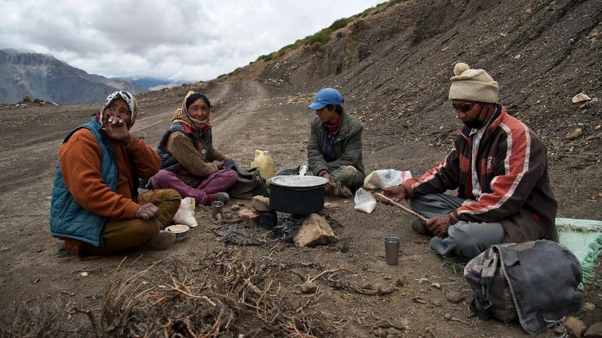 In this Aug. 17, 2016, photo, from left to right, Chhering Chodom, 60, Tashi Yangzom, 50, Lobsang Chhering, 27, and Dorje Tandup, 58, drink milk tea on the side of the road. For centuries, the sleepy valley nestled in the Indian Himalayas remained a hidden Buddhist enclave forbidden to outsiders. That's all now starting to change since India began allowing its own citizens as well as outsiders to visit the valley in the early 1990s. Some villagers and travelers worry the influx of new funds will bring competition, greed and environmentally taxing change, such as flush toilets that might empty straight into the Spiti River, or a strain on the region's already limited water sources. (AP Photo/Thomas Cytrynowicz)