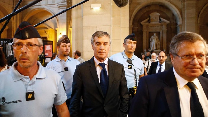 Former French budget Minister Jerome Cahuzac, center, with one of his lawyer Jean Veil, right, is escorted by French Gendarmes as he leaves the courthouse, in Paris, Wednesday, Sept. 14, 2016. Cahuzac appeared in a Paris court on charges of tax fraud and money laundering that saw him resign in 2013 in one of the biggest political scandals under President Francois Hollande. The prosecutor asked the judge Wednesday to sentence Cahuzac to three years in prison. (AP Photo/Francois Mori)