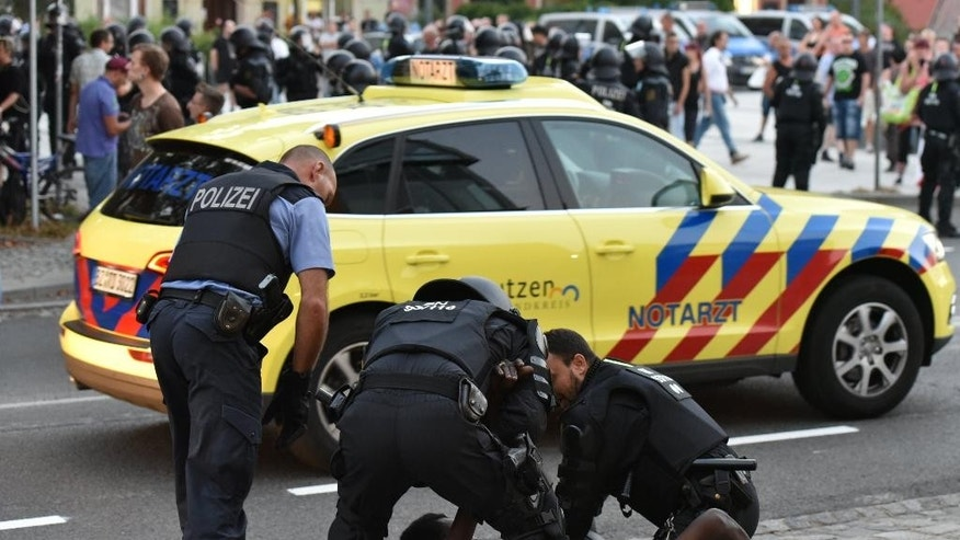 In this Sept. 10, 2016 photo police officers take a man into custody during a gathering on a square at the Kornmarkt in Bautzen, Germany. Police reported verbal and violent attacks have erupted between about 80 far-right activists and about 20 young asylum seekers. (Christian Essler, XCITEPRESS/dpa via AP)