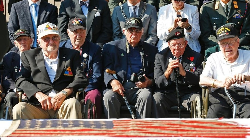World War II veterans sit behind an American flag carried during D-Day in 1944 after it arrived at the National Military Museum in Soesterberg, Netherlands, Thursday, Sept. 15, 2016. The American 48-star flag was flown on the stern of the US Navy ship LCC 60, which was the leading vessel on 6 June 1944, responsible for directing the invasion fleet and the first American troops to Utah Beach in Normandy, France. (AP Photo/Peter Dejong)