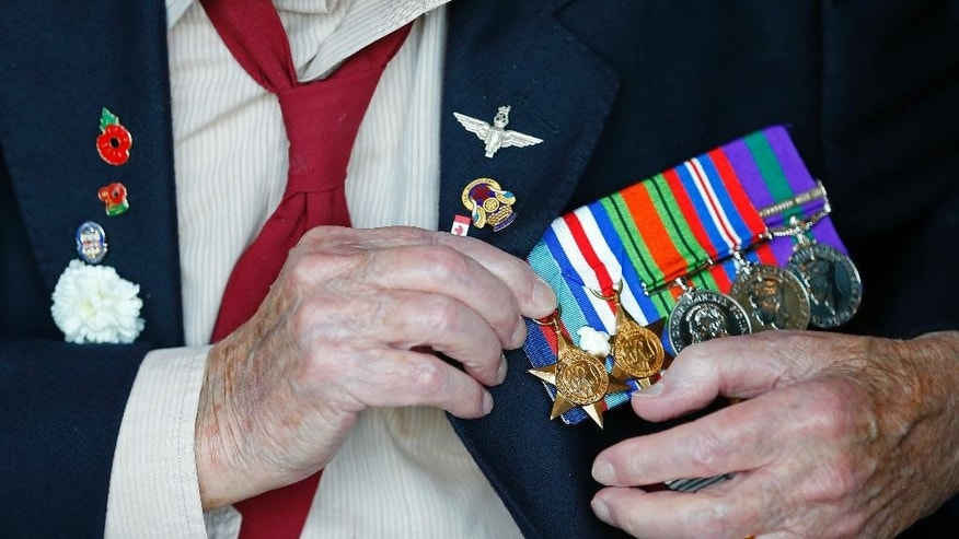 A World War II veteran adjusts his medals prior to the arrival ceremony for an American flag carried during D-Day in 1944 at the National Military Museum in Soesterberg, Netherlands, Thursday, Sept. 15, 2016. The American 48-star flag was flown on the stern of the US Navy ship LCC 60, which was the leading vessel on 6 June 1944, responsible for directing the invasion fleet and the first American troops to Utah Beach in Normandy, France. (AP Photo/Peter Dejong)