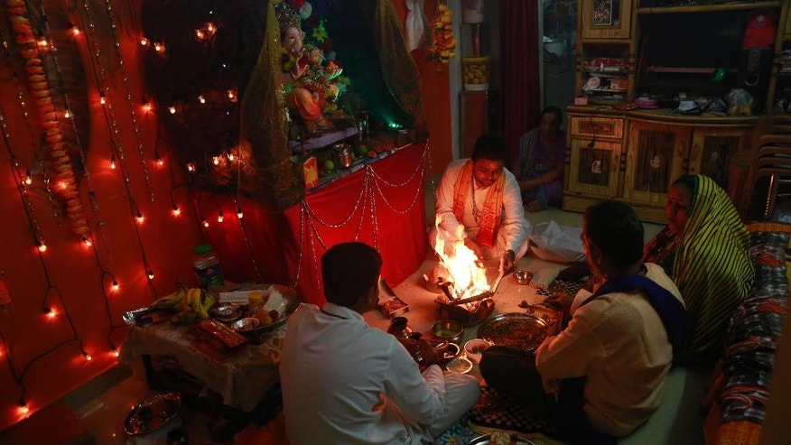 "In this Tuesday, Sept. 6, 2016 photo, Raju Laljibhai Dipikar, 50, second right, along with his wife Padma and Hindu priests offer prayers to an idol of elephant-headed Hindu god Ganesha at his home, on the second day of Ganesha Chaturthi festival in Mumbai, India. Every year Dipikar goes out with his family to choose an elaborate statue of the Ganesha and for two days the god ""lives"" with the family in their tiny apartment in Mumbai, his very presence bringing them joy. And in return for the love the family showers on him he takes away all their problems, Dipikar says. (AP Photo/Rafiq Maqbool)"