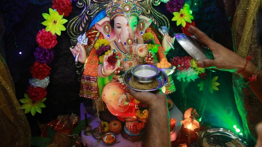 "In this Tuesday, Sept. 6, 2016 photo, Raju Laljibhai Dipikar offers kheer, an Indian sweet, to an idol of elephant-headed Hindu god Ganesha at their house on the second day of Ganesha Chaturthi festival in Mumbai, India. Every year Dipikar goes out with his family to choose an elaborate statue of the Ganesha and for two days the god ""lives"" with the family in their tiny apartment in Mumbai, his very presence bringing them joy. And in return for the love the family showers on him he takes away all their problems, Dipikar says. (AP Photo/Rafiq Maqbool)"