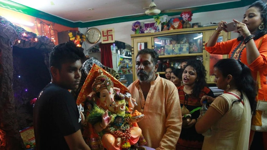 "In this Tuesday, Sept. 6, 2016 photo, Raju Laljibhai Dipikar and a relative carry an idol of elephant-headed Hindu god Ganesha to take it out of his house for immersion on the second day of Ganesha Chaturthi festival in Mumbai, India. Every year Dipikar goes out with his family to choose an elaborate statue of the Ganesha and for two days the god ""lives"" with the family in their tiny apartment in Mumbai, his very presence bringing them joy. And in return for the love the family showers on him he takes away all their problems, Dipikar says. While families immerse the idols installed in their homes at different points in the ten-day celebration, it's the tenth day that makes for the most grand spectacle. (AP Photo/Rafiq Maqbool)"