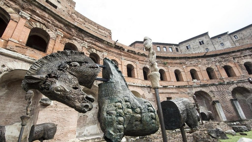 A sculpture of a horse stands in ancient Rome's Trajan's Market as part of an itinerant exhibit, Lapidarium, by the Mexican artist Gustavo Aceves, which opened in Rome, Thursday, Sept. 15, 2016. The exhibit, made up of forty grim horses made of bronze, iron, marble and granite, is intended to raise awareness about the ongoing migrant crisis. (Massimo Percossi/ANSA via AP)