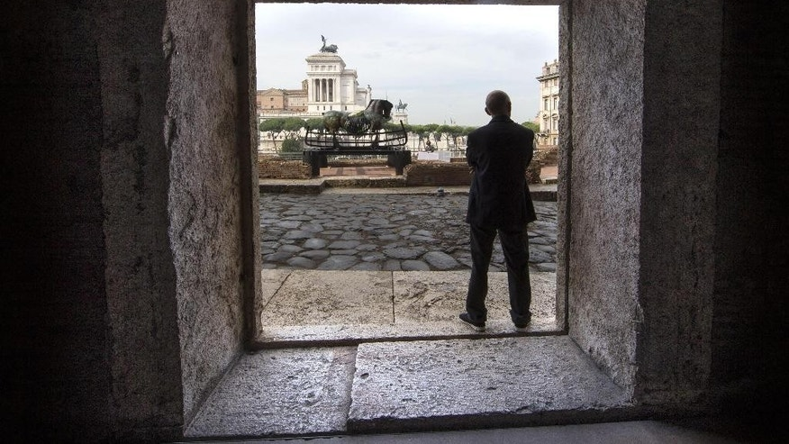 A sculpture of a horse is framed through a window of Rome's ancient Trajan's Market as part of an itinerant exhibit, Lapidarium, by the Mexican artist Gustavo Aceves, which opened in Rome, Thursday, Sept. 15, 2016. The exhibit, made up of forty grim horses made of bronze, iron, marble and granite, is intended to raise awareness about the ongoing migrant crisis. (Massimo Percossi/ANSA via AP)