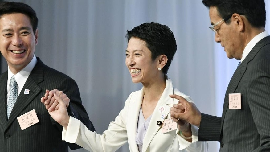 Newly elected Democratic Party leader Renho Murata, center, smiles as she joins hands with her predecessor Katsuya Okada, right, and her rival candidate for the leadership race Seiji Maehara upon her election in Tokyo Thursday, Sept. 15, 2016. Murata, who generally goes by only her first name, is a woman, one of three who have assumed prominent political posts in recent weeks in a country more known for its male-dominated political and business hierarchy. Her election to the new head of Japan's main opposition party Thursday followed that of Tokyo's first female leader on July 31, and the appointment of a woman as defense minister later the same week. (Shigeyuki Inakuma/Kyodo News via AP)
