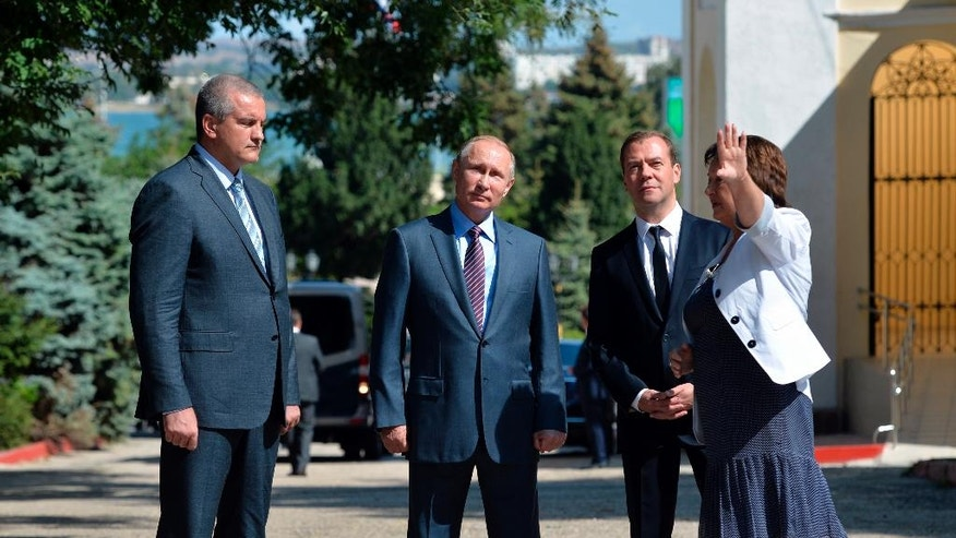 From left, Crimean leader Sergei Aksyonov, Russian President Vladimir Putin and Russian Prime Minister Dmitry Medvedev listen to Crimean Museum director Tatyana Umrikhina in Kerch, Crimea on Thursday, Sept. 15, 2016. Russian President Vladimir Putin is due to hold a Presidential Security Council meeting and attend an event at the Kerch Bridge site. (Alexei Druzhinin/Sputnik, Kremlin Pool Photo via AP)