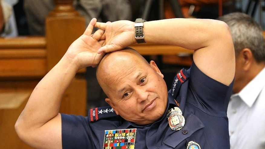 Philippine Police Chief Ronald Dela Rosa stretches during a break at a senate committee hearing where a former Filipino militiaman Edgar Matobato testified at the Philippine Senate in Pasay, south of Manila, Philippines on Thursday Sept. 15, 2016. Matobato said that Philippine President Rodrigo Duterte, when he was still a city mayor, ordered him and other members of a squad to kill criminals and opponents in gangland-style assaults that left about 1,000 dead. (AP Photo/Aaron Favila)