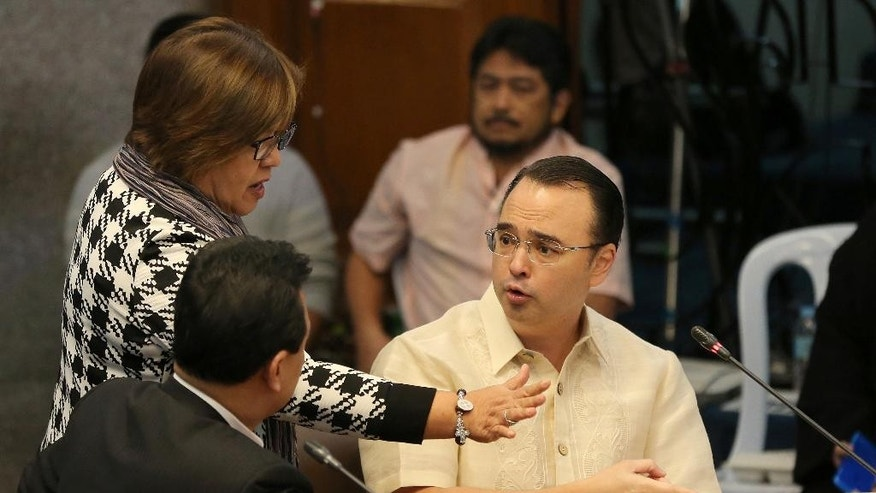 Philippine Senator Leila de Lima, center, Chairperson of the Commitee on Justice and Human Rights, tries to pacify an argument between Senator Allan Peter Cayetano, right, and Senator Antonio Trillanes IV as they question former Filipino militiaman Edgar Matobato at the Philippine Senate in Pasay, south of Manila, Philippines on Thursday Sept. 15, 2016. Matobato said that Philippine President Rodrigo Duterte, when he was still a city mayor, ordered him and other members of a squad to kill criminals and opponents in gangland-style assaults that left about 1,000 dead. (AP Photo/Aaron Favila)