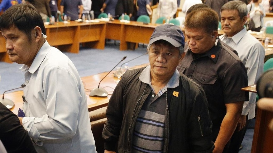 Former Filipino militiaman Edgar Matobato, center, walks under tight security after testifying at the Philippine Senate in Pasay, south of Manila, Philippines on Thursday, Sept. 15, 2016. Matobato said that Philippine President Rodrigo Duterte, when he was still a city mayor, ordered him and other members of a squad to kill criminals and opponents in gangland-style assaults that left about 1,000 dead. (AP Photo/Aaron Favila)
