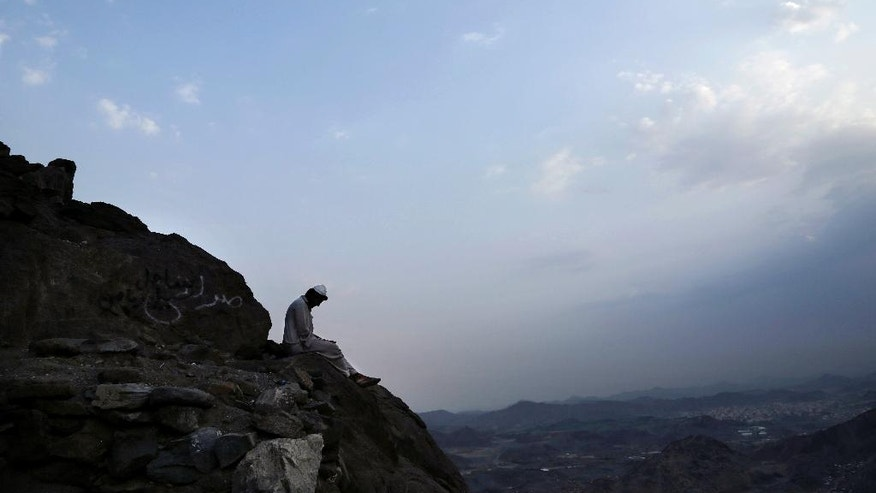 In this Friday, Sept. 9, 2016 photo, a Pakistani man living near Hira cave reads before sunrise on Noor Mountain, where the Prophet Muhammad received his first revelation from God to preach Islam, on the outskirts of Mecca, Saudi Arabia. It is one of Islam's most important historical sites _ the cave where the Prophet Muhammad spent time in seclusion, contemplation and self-reflection.(AP Photo/Nariman El-Mofty)
