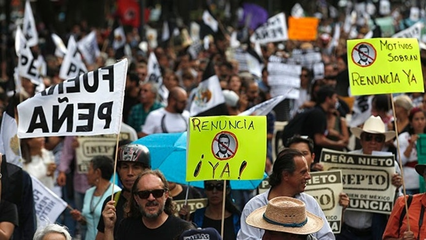 People march to demand the resignation of Mexico's President Enrique Pena Nieto in Mexico City, Thursday, Sept. 15, 2016, one day before the country's independence day. (AP Photo/Eduardo Verdugo)