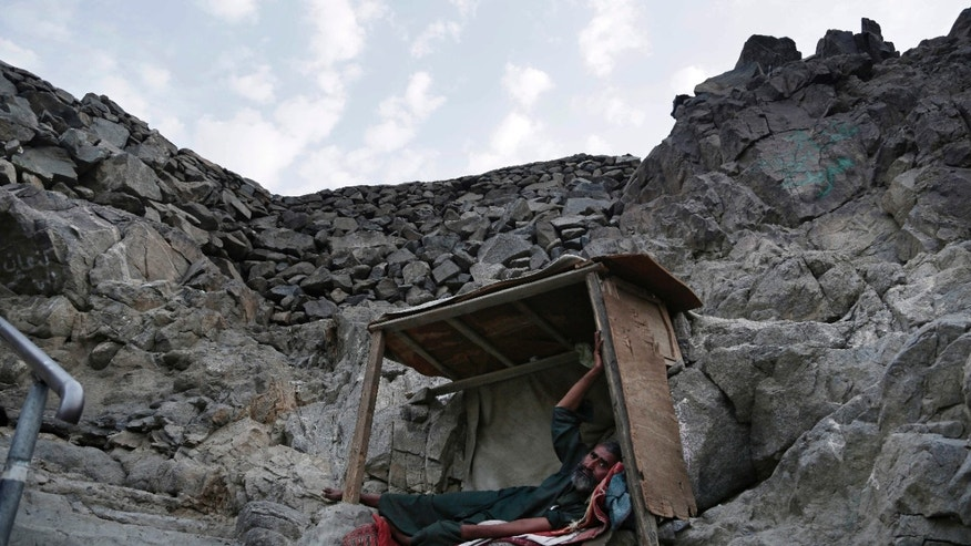 In this Friday, Sept. 9, 2016 photo, a Pakistani beggar who sleeps on Noor Mountain, where Prophet Muhammad received his first revelation from God to preach Islam, poses for a portrait, on the outskirts of Mecca, Saudi Arabia.