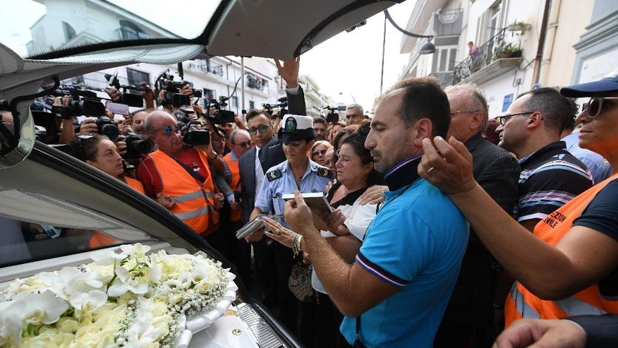 Members of the media crowd around the hearse of Tiziana Cantone as her mother Teresa Giglio, center, salutes it, during her funeral in Casalnuovo, near Naples, Italy, Thursday, Sept. 15, 2016. Italian prosecutors in Naples have opened an investigation into possible charges of instigation to suicide after a 31-year-old woman killed herself after failing in a long legal battle to get a pornographic video removed from the Internet.  (Ciro Fusco/ANSA via AP)