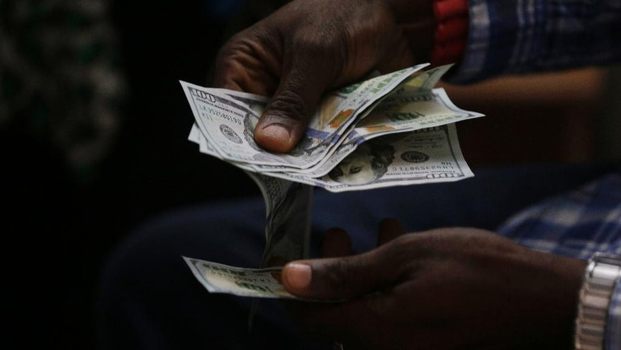 In this photo taken on Monday, June 20, 2016, a trader counts US Dollars inside a shop in Lagos, Nigeria. Nigeria soon will sell $1 billion in Eurobonds to finance a budget deficit as a recession grips the major African oil producer amid foreign currency shortages and double-digit inflation, officials said Friday, Sept. 16, 2016. (AP Photo/Sunday Alamba)