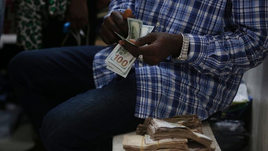 In this photo taken on Monday, June. 20, 2016, a trader counts US Dollars inside a shop in Lagos, Nigeria. Nigeria soon will sell $1 billion in Eurobonds to finance a budget deficit as a recession grips the major African oil producer amid foreign currency shortages and double-digit inflation, officials said Friday. Sept.16, 2016. (AP Photo/Sunday Alamba)