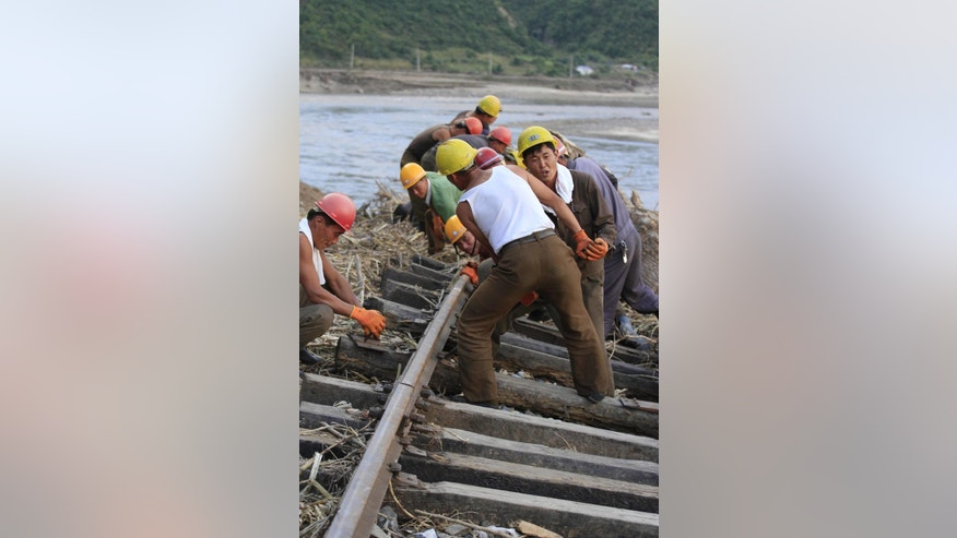 Workers repair the flood-damaged train track between Sinjon and Kanphyong train stations in North Hamgyong Province, North Korea, Friday, Sept. 16, 2016. North Korean soldiers and relief teams rushed to clear roads and railway tracks, build shelters and provide food and sanitation Friday to tens of thousands of residents in a remote part of the country near the Chinese border that was devastated by heavy downpours and flash-floods when a typhoon pounded their villages last week. (AP Photo/Kim Kwang Hyon)