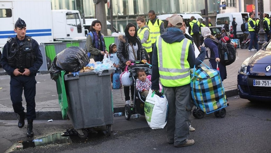 Migrants are evacuated from a temporary camp in the north of Paris, Friday, Sept. 16, 2016. Police and city officials are evacuating hundreds of migrants who had been living on the streets of northern Paris for weeks, in the latest of a string of attempts to find solutions for France's migrants. (AP Photo/Thibault Camus)