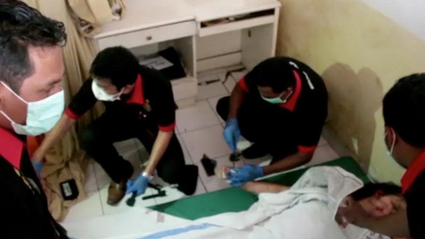 This image made from video shows paramedics examining the body of a foreign tourist who was killed in a boat explosion at a hospital in Karangasem, Bali, Indonesia on Thursday, Sept. 15, 2016. The explosion occurred not long after the boat departed from the resort island of Bali to ferry tourists to nearby island of Lombok. (AP Photo)