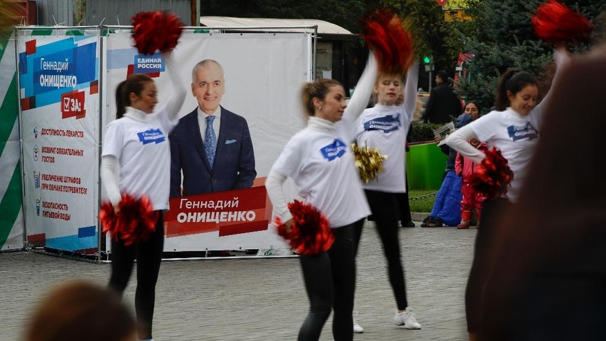 Dancers perform in front of an election poster of the Kremlin-backed United Russia party in Moscow, Russia, Thursday, Sept. 15, 2016. Russia's parliamentary election will be held on Sunday. (AP Photo/Pavel Golovkin)