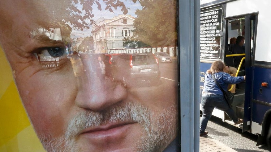 An election poster with a portrait of Just Russia party leader Sergei Mironov is placed in St. Petersburg, Russia, Thursday, Sept. 15, 2016. Russia's parliamentary election will be held on Sunday. (AP Photo/Dmitri Lovetsky)