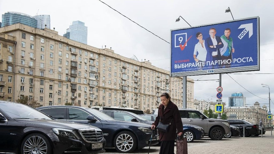 A woman walks in front of an election poster of the Party of Growth in Moscow, Russia, Thursday, Sept. 15, 2016. Russia's parliamentary election will be held on Sunday. (AP Photo/Alexander Zemlianichenko)