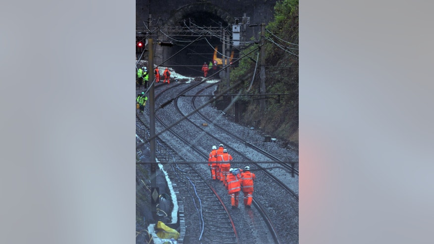 Workers attend the scene of a the landslip near Watford Junction station, England, which has caused a train to be derailed Friday Sept. 16, 2016.  A London-bound passenger train hit a landslip triggered by heavy rain and derailed, causing no injuries but major disruption. Train operator London Midland said part of the train derailed and hit an oncoming train near Watford Junction, 20 miles (32 kms) north of London on Friday morning. (Steve Parsons/PA via AP)