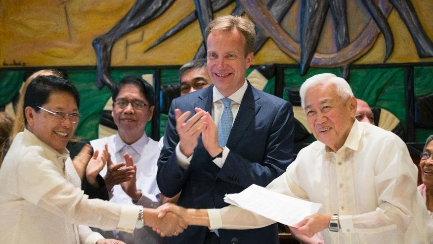 FILE - In this Aug. 26, 2016 file photo, Jesus Dureza, left, representative of the Philippine government, and Luis Jalandoni, representative of the communist movement National Democratic Front of the Philippines, right, shake hands as Norwegian Foreign Minister Boerge Brende, center, applauds after the signing of a joint declaration in which both parties undertake unilateral ceasefires without time constraints. Ransom-seeking Abu Sayyaf extremists on Saturday, Sept. 17, freed a Norwegian man kidnapped a year ago in the southern Philippines along with two Canadians who were later beheaded and a Filipino woman who has been released, officials said. Dureza, who advises Philippine President Rodrigo Duterte on peace talks with insurgent groups, said Kjartan Sekkingstad, held in jungle captivity since being kidnapped last September, was to stay overnight at the house of Moro National Liberation Front chairman Nur Misuari in Sulu and then meet with Duterte on Sunday. (Berit Roald/NTB via AP, File)