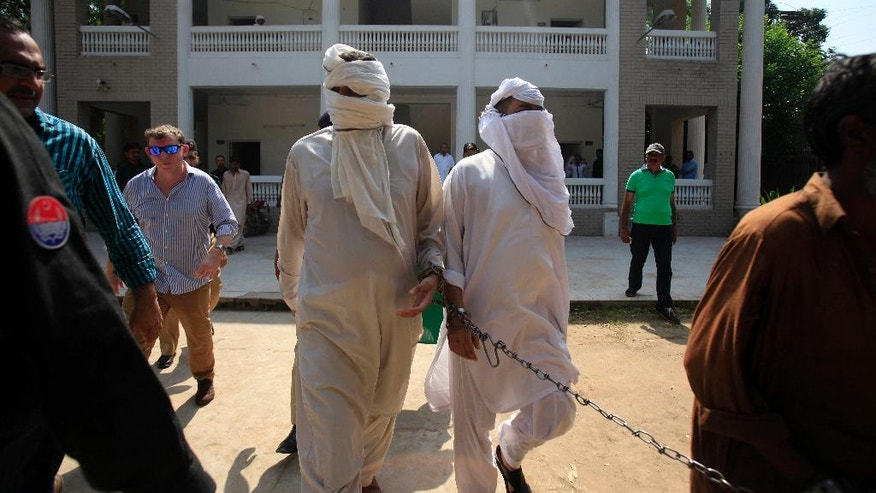 Handcuffed father Muhammad Shahid, center left, and ex-husband Muhammad Shakeel, center right, of slain British-Pakistani woman Samia Shahid are escorted by Pakistani police officers following their court appearance in Jhelum in eastern Pakistan, Saturday, Sept. 17, 2016. A Pakistani court on Saturday adjourned the case of Samia Shahid's murder until Sept. 23 to give police more time to submit charges against them who are accused of slaying her in the name of honor, police and lawyers said. (AP Photo/Anjum Naveed)