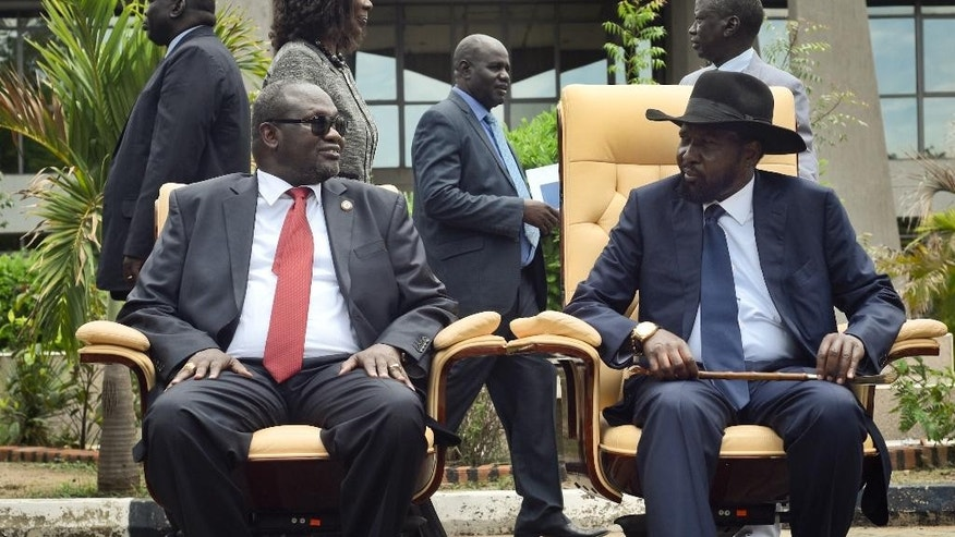 FILE - In this Friday, April 29, 2016 file photo, the then South Sudan's First Vice President Riek Machar, left, looks across at President Salva Kiir, right, as they sit to be photographerd following the first meeting of a new transitional coalition government, in the capital Juba, South Sudan. A new report Monday, Sept. 12, 2016 by a U.S.-based watchdog group accuses South Sudan's rival leaders of amassing wealth abroad amid a conflict in which tens of thousands have been killed. (AP Photo/Jason Patinkin, File)