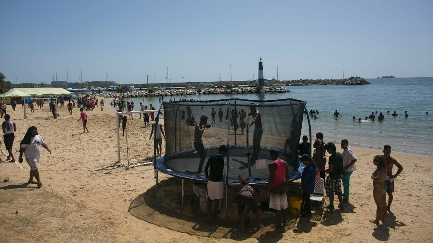 Youth jump on a trampoline set up on the beach at a pro-government camp in Porlamar on Margarita Island, Venezuela, Friday, Sept. 16, 2016. Hundreds of teenage activists are sleeping in tents and enjoying free concerts on the beach as foreign delegates arrive to attend the non-aligned summit held by a Cold War-era group of 120 nations. (AP Photo/Ariana Cubillos)