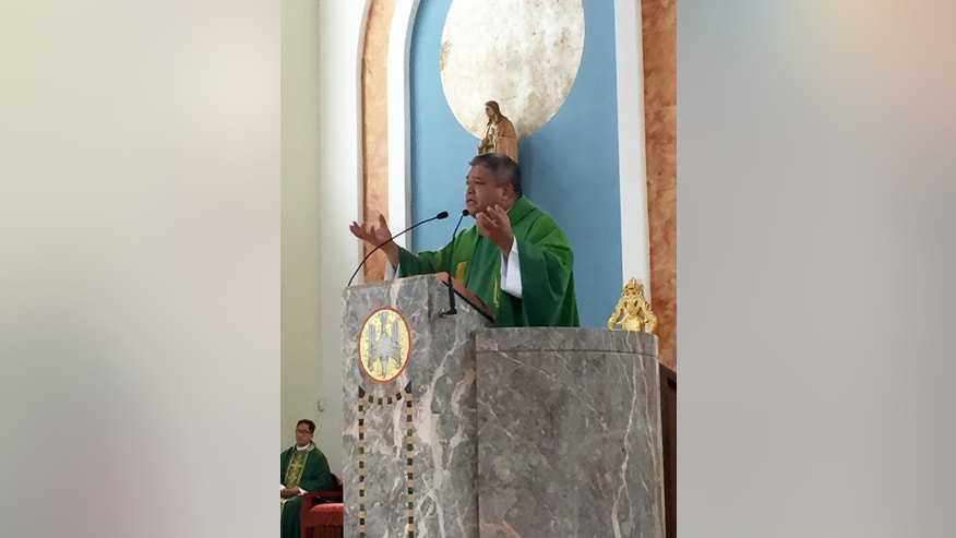 Rev. Fr. Jeffrey C. San Nicolas, apostolic delegate, delivers a homily on Sunday, Sept. 18, 2016, at the Dulce Nombre de Maria Cathedral-Basilica in Hagatna, Guam. During the same Mass he read a letter from Archbishop Savio Tai Fai Hon, Apostolic Adminstrator, who called for the Holy See to remove Archbishop Anthony S. Apuron from his position. Apruon, 70, was appointed as archbishop in 1986 by then-Pope John Paul II and has been beset by recent allegations from former altar boys that he sexually abused them in the 1970's. (AP Photo/Grace Garces Bordallo)