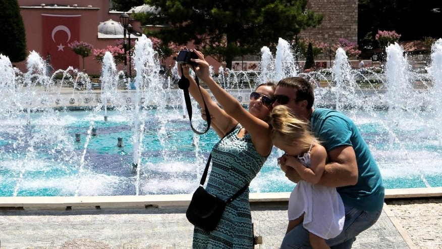 FILE - In this Tuesday, July 26, 2016 file photo,  tourists take a selfie at the Byzantine-era Hagia Sophia, in the historic Sultanahmet district of Istanbul. With summer drawing to a close, Turkey is counting the cost of a tough year that saw a string of terrorist bombings and a diplomatic spat with Moscow that cut deep into the country's crucial tourist trade. (AP Photo/Petros Karadjias, File)