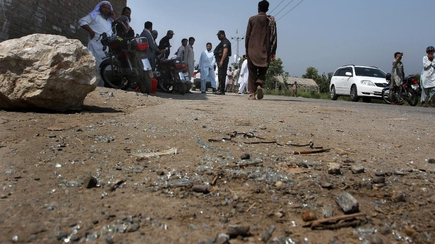 Pakistani police officers and local residents gather at the site of firing incident at Garhi Sohbat Khan on the outskirts of Peshawar, Pakistan, Sunday, Sept. 18, 2016. Two gunmen on a motorcycle killed three soldiers Sunday, police said. (AP Photo/Mohammad Sajjad)