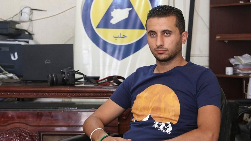 """Ibrahim Alhaj, 26-year old member of Syrian Civil Defense, also known as White Helmets, sits in front of a banner for the first responders rescue group in Aleppo, Syria, in Aug. 2016. Alhaj says the cease-fire has allowed him some rest time from the grueling task of documenting rescue efforts and documents any """"double-tap"""" attacks a common government tactic of striking a target again shortly after the first hit to cause more casualties. War-hardened residents of Aleppo's eastern districts one of the last large urban centers defying President Bashar Assad are skeptical the cease-fire will hold. (Handout from Ibrahim Alhaj via AP)"""