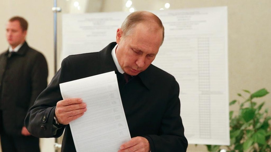 Russian President Vladimir Putin casts his ballot at a polling station during a parliamentary election in Moscow, Russia, Sunday, Sept. 18, 2016. Russia's weekend parliament elections take place under new rules that in principle could bring genuine opposition into the national legislature. (Grigory Dukor/ pool photo via AP)