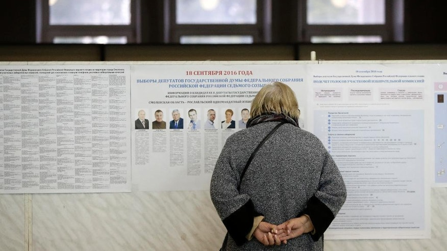 A woman reads pre-election leaflets at a polling station in Smolensk, western Russia, Sunday, Sept. 18, 2016. Russia's governing party and its three largely cooperative opponents are expected to retain their positions in the national parliament, but new procedures for choosing the seats could affect their proportions. (AP Photo/Sergei Grits)