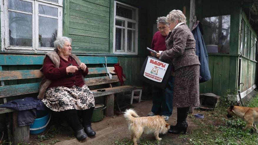 An election commission official talks with voters, outside their home in the village of Gusino, outside Smolensk, western Russia, Sunday, Sept. 18, 2016. Russia's governing party and its three largely cooperative opponents are expected to retain their positions in the national parliament, but new procedures for choosing the seats could affect their proportions. (AP Photo/Sergei Grits)