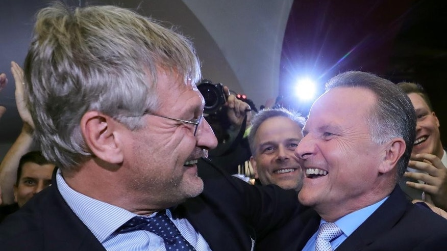 Alternative for Germany party chairman Joerg Meuthen, left, and Georg Pazderski, AfD's State Chairman and top candidate for Alternative for Germany for the state elections in Berlin, celebrate after the first exit polls were published in Berlin, Germany, Sunday, Sept. 18, 2016 (Michael Kappeler/dpa via AP)