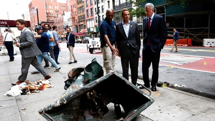 New York Mayor Bill de Blasio, right, and New York Governor Andrew Cuomo, second right, look over a mangled construction toolbox Sunday, Sept. 18, 2016, while touring the site of an explosion that occurred on Saturday night in the Chelsea neighborhood of New York. Numerous people were injured in blast, and the motive, while reportedly not international terrorism, is still being investigated. (Justin Lane/EPA via AP, Pool)