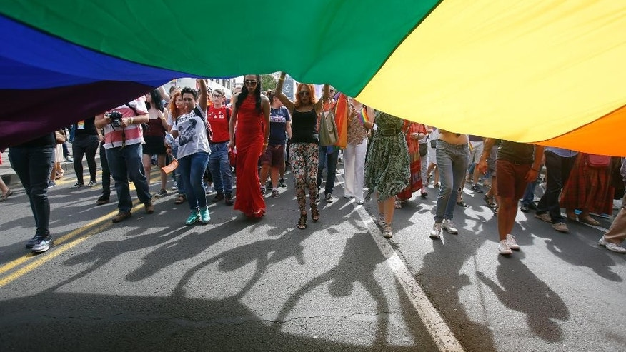 People wave flags during a gay pride march in Belgrade, Serbia, Sunday, Sept. 18, 2016. Thousands of Serbian riot police have cordoned off central Belgrade for a gay pride march amid fears attacks from extremists in the predominantly conservative Balkan country seeking European Union membership. (AP Photo/Darko Vojinovic)