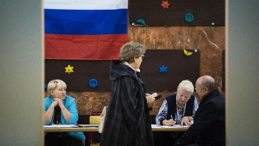 People register to get ballot papers at a polling station during a parliamentary elections in Moscow, Russia, Sunday, Sept. 18, 2016. Russia's weekend parliament elections take place under new rules that in principle could bring genuine opposition into the national legislature. (AP Photo/Pavel Golovkin)