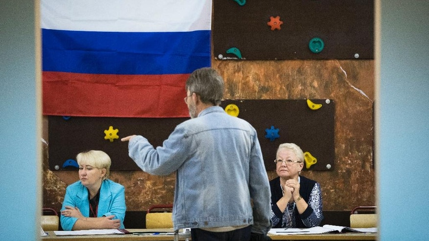 A man talks to election commission officials at a polling station during a parliamentary elections in Moscow, Russia, Sunday, Sept. 18, 2016. Russia's weekend parliament elections take place under new rules that in principle could bring genuine opposition into the national legislature. (AP Photo/Pavel Golovkin)