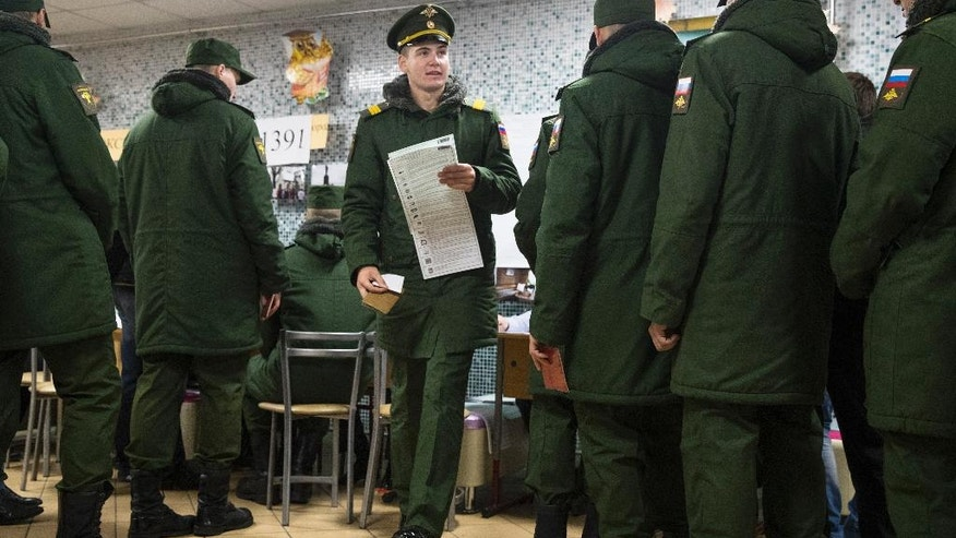 A Russian army officer holding a ballot walks through military cadets lining up to get their ballots at a polling station during a parliamentary election in Moscow, Russia, Sunday, Sept. 18, 2016. Russia's governing party and its three largely cooperative opponents are expected to retain their positions in the national parliament, but new procedures for choosing the seats could affect their proportions. (AP Photo/Pavel Golovkin)